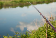 Fishing rod on the Bank of the river, the sky reflected in the water of the river Stock Photos