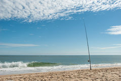 Sunny day on a beach with fishing rod. Fishing rod sticking out in the sand on a beach in France Stock Images