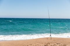 Fishing rod on beach on sunny day stock image