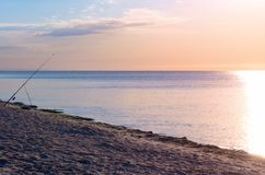 Fishing rod on the beach, sunrise reflected on the watery surface, horizon calm. sea shore. Toning stock photos