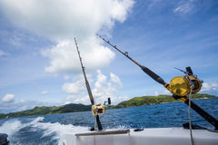 Fishing rod on boat at sea. Fishing rod and reel on side of boat with blue sea in background Stock Photography