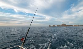 Fishing rod on charter fishing boat on the Sea of Cortes / Gulf of California viewing Lands End at Cabo San Lucas Baja Mexico. BCS royalty free stock photography
