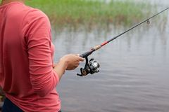 Fishing rod with a fishing reel in a woman`s hand. Red clothes Royalty Free Stock Image