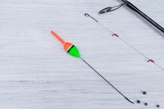 Fishing rod and float with fishing line lie on a light background royalty free stock photo