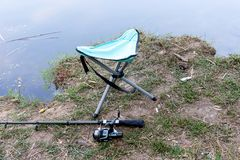 Fishing rod, folding stool, float and other gear on the river bank. Fishing rod, folding stool, float and other gear on the river bank royalty free stock image