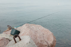 Fishing rod and green bucket lying on the stone on sea background Royalty Free Stock Image