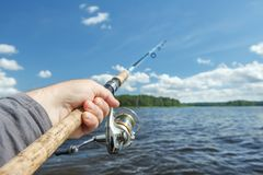 Fishing rod in hand on the background of the shore, covered with. Green forest.Blue sky and water Royalty Free Stock Images