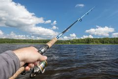 Fishing rod in hand on the background of the shore, covered with. Green forest.light waves Royalty Free Stock Images
