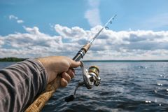Fishing rod in the hand on the background of a wide river on a s. Unny day.Focus on hand Royalty Free Stock Photography