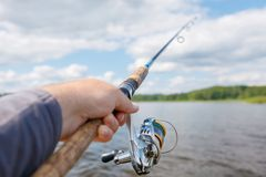 Fishing rod in a hand on a blurred forest background. Focus on fishing reel Stock Image