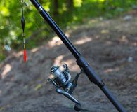 Fishing rod with inertialess reel and  float. Royalty Free Stock Photography