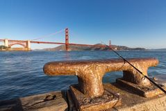 Fishing rod on an iron dock cleat. Royalty Free Stock Images