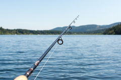 Fishing rod on a lake with mountains. In the background Royalty Free Stock Photos