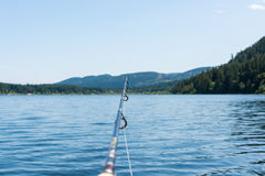 Fishing rod on a lake with mountains. In the background Royalty Free Stock Image