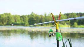 Fishing rod on the lake in summer day. Professional fishing rod waiting for bites on water river. Fishing rod on the lake in summer day stock video footage