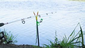Fishing rod on the lake in summer day. Professional fishing rod waiting for bites on water river. Fishing rod on the lake in summer day stock footage