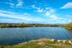 Fishing rod on the lakeside on a beautiful sunny day Royalty Free Stock Image