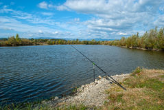 Fishing rod on the lakeside on a beautiful sunny day Royalty Free Stock Photography