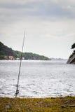 Fishing rod left alone on lake shore Royalty Free Stock Images