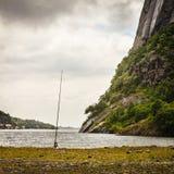 Fishing rod left alone on lake shore Royalty Free Stock Image