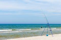 Fishing rod left alone on sea shore Royalty Free Stock Photo