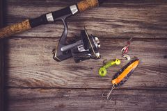 Fishing rod with lure over wood Royalty Free Stock Images