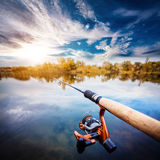 Fishing rod near beautiful pond with cloudly sky Royalty Free Stock Photos
