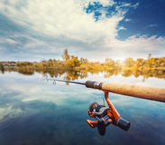 Fishing rod near beautiful pond with cloudly sky Royalty Free Stock Image