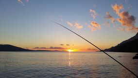 Fishing Rod Near Body of Water during Sunset Royalty Free Stock Photo