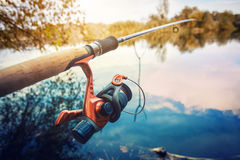 Fishing rod near pond in the morning Stock Images
