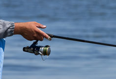 Fishing rod over the blue water Stock Images