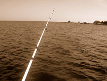 Fishing rod over sea. Black and white scenic view of long fishing rod over sea Royalty Free Stock Photo