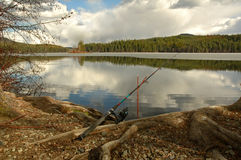 Fishing rod placed on the ground near a lake. Outdoors at a recreational area stock image
