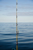 Fishing rod pointed to the open water. Fishing rod with the still water on the background Stock Photography