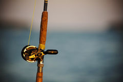Fishing Rod and Reel. Close up image of a vintage fishing rod and reel with shallow depth of field and blue ocean in the background royalty free stock photo