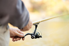 Fishing Rod and Reel. Fisherman holding Fishing Rod with Reel. Selective focus. Focus on Reel Royalty Free Stock Photo