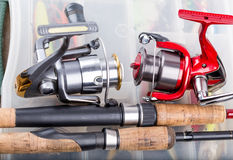 Fishing rod with reel on background of tackles in boxes Stock Image