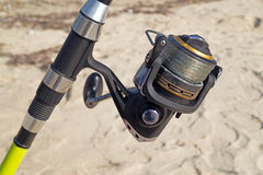 Fishing rod and reel on the beach Royalty Free Stock Photos