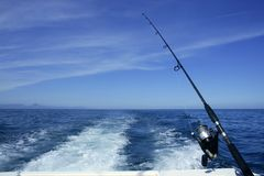 Fishing rod and reel on boat. Fishing rod and reel on a boat, vacation on blue sea and summer sky Stock Image
