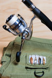 Fishing rod and reel with fishing vest. Royalty Free Stock Images