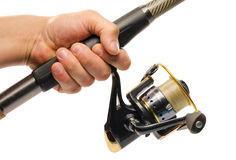 Fishing rod and reel. Hand holding a fishing rod and reel, closeup on a white background is insulated stock images