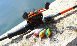 Fishing rod and reel with lures. Bait casting fishing rod and reel with lures Royalty Free Stock Photo