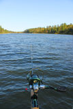 Fishing Rod and Reel over Lake in Northern Minnesota. A fishing rod and reel extended into a clear blue lake in Itasca State Park in northern Minnesota Royalty Free Stock Photo