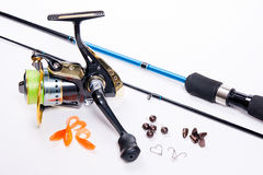 Fishing rod and reel with silicone baits on white. Stock Photo