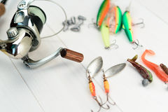 Fishing rod with reel, spoon baits, tackles and wobblers in box for catching or fishing a predatory fish on white vintage wooden b Royalty Free Stock Image