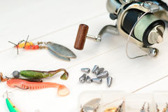 Fishing rod with reel, spoon baits, tackles and wobblers in box for catching or fishing a predatory fish on white vintage wooden b Royalty Free Stock Photography