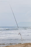 Fishing rod in the sand Coastline blurred in background Royalty Free Stock Photo