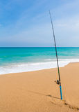 Fishing rod in sand of tropical beach the sea Royalty Free Stock Photo