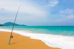 Fishing rod in sand of tropical beach Stock Image