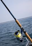 Fishing rod and sea. Closeup of fishing rod and reel with sea in background stock photo